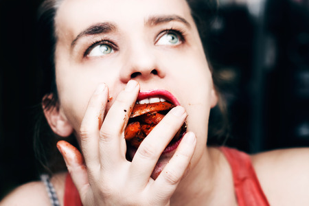 binge: Woman binge eating french fries, mouth full of food