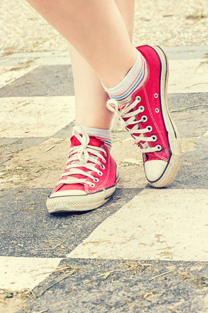 Womans legs in red canvas sneakers Stock Photo