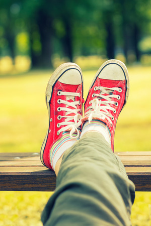 Womans feet in a red canvas sneakers sitting on a bench