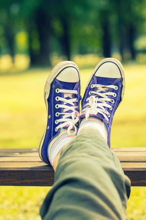 Womans feet in a dark blue canvas sneakers sitting on a bench Stock Photo