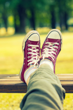 Womans feet in a dark red canvas sneakers sitting on a bench