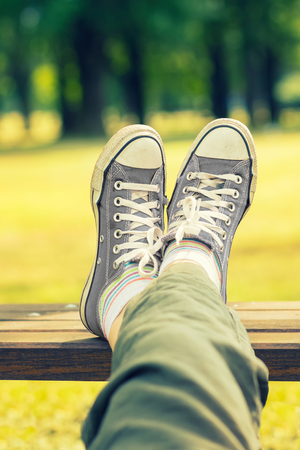 Womans feet in a grey canvas sneakers sitting on a bench