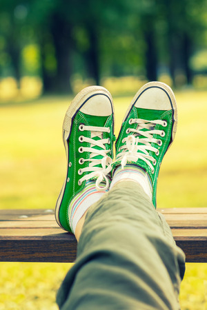 Womans feet in a green canvas sneakers sitting on a bench Stock Photo