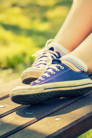 Womans feet in a dark blue canvas sneakers sitting on a bench.