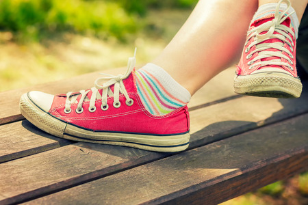 Womans feet in a red canvas sneakers relaxing on a bench. Stock Photo
