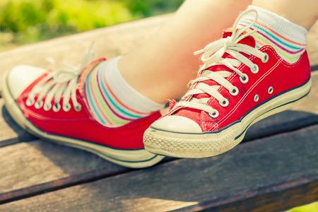 빨간색 캔버스에 여자의 발 운동 화 벤치에서 휴식.