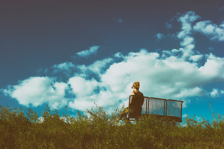 bench alone: Woman in the distance, sitting on bench on a grass hill top, alone and lonely Stock Photo