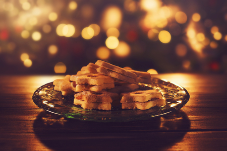 Jam filled Christmas cookies on a glass plate in low golden light with some bokeh in bacground