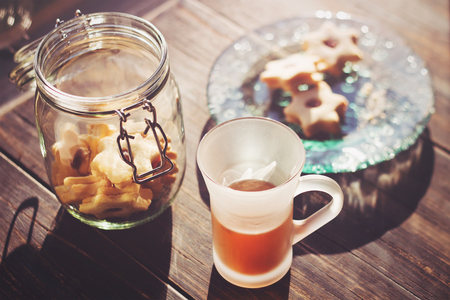 strawberry jam sandwich: Jam filled cookies on a glass plate on wooden table with cup of tea in the morning light