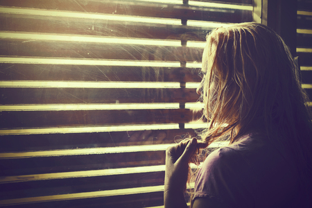 heartbreak issues: Sad and lonely blonde woman with wet hair looking through window blinds into the sunlight