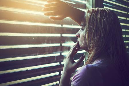 68506241-la-mujer-rubia-triste-y-solo-con-el-pelo-mojado-mirando-a-trav%C3%A9s-de-persianas-de-la-ventana-en-la-luz-.jpg?ver=6