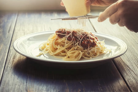 Freshly cooked spaghetti bolognese on a white plate and with female hands grating parmesan cheese