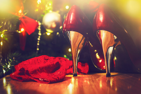 Shiny red and silver high heels under the Christmas tree Stock Photo