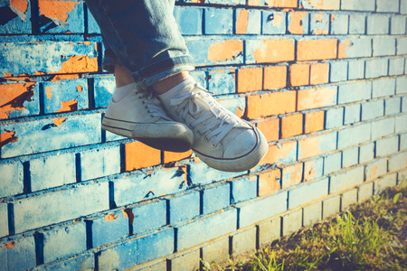 sulight: Female legs in white canvas sneakers and jeans dangling from a blue brick wall on a sunny summer day