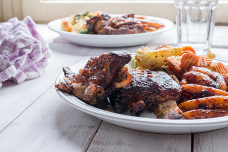 Côtes cuites au four avec des pâtes maison et des légumes grillés servis sur une table en bois Banque d'images - 83288163