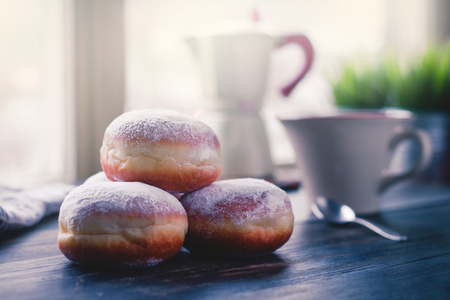 Jelly filled doughnuts on a kitchen table in the morning, coffee mug and pot in the background