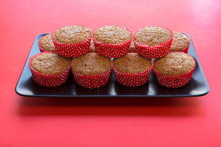 Bran muffins in bright red and white paper holders on a black rectangular plate and red background