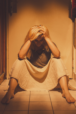Sad, depressed and lonely woman sitting on a floor tiles, in a skirt, barefoot with a long blond hair Stock Photo