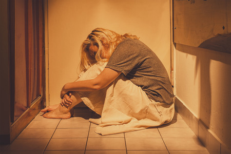 Sad, depressed and lonely woman sitting in a corner on a floor tiles, in a skirt, barefoot with a long blond hair Banque d'images