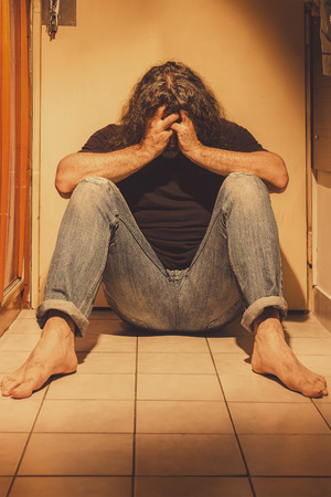 Man sitting on a floor tiles, sad, depressed and lonely