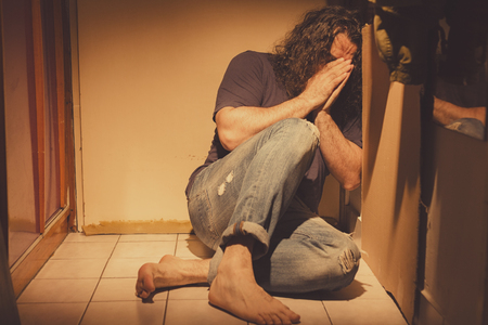 Man lying in a corner, sad, depressed and lonely, crying