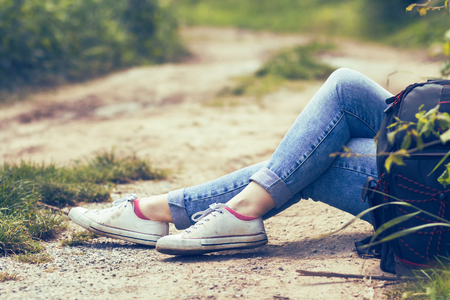 Woman sitting by the dirt road, in blue jeans and white canvas sneakers, backpack by her side, resting