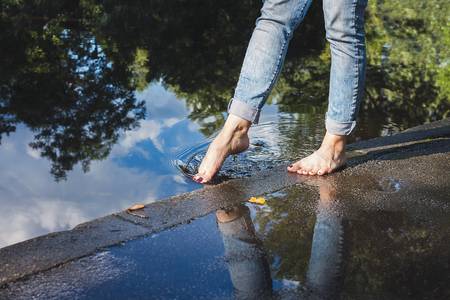물에 의해 포장에 서있는 청바지에서 맨발의 여자, 발가락을 물속에 담그다
