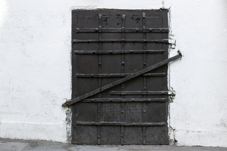 black metallic background: Black iron door with bolts on white wall