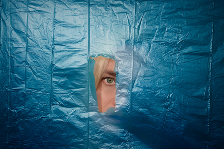 peephole: Womans eye looking through torn off blue nylon barrier Stock Photo