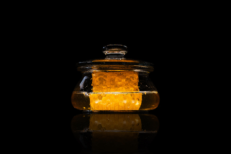 Shiny jar of honey with piece of beeswax, in glass container on a black background, with reflection