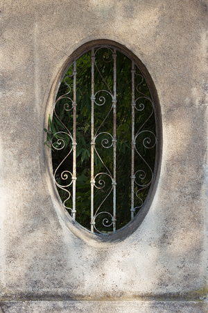 Stone fence with circular opening and wrought iron bars Stock Photo
