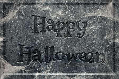 Tombstone with engraved words Happy Halloween covered in cobwebs Stock Photo