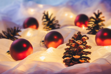 Red Christmas baubles, pine cones and Christmas lights on white background