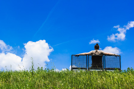 Man sitting on a bench atop grass hill, blue sky and white clouds in background