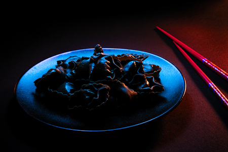 Plate of black dumplings, on a black plate with pair of red chopsticks, illuminated with blue light from TV screen