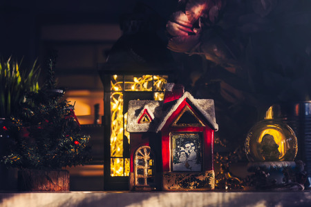 Christmas ornaments on the shelf, little red house, lantern and snow globe illuminated with sunlight
