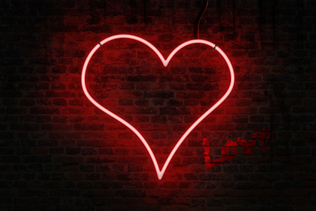 Red neon heart shaped sign on a brick wall, with word love written in a red paint Stock Photo