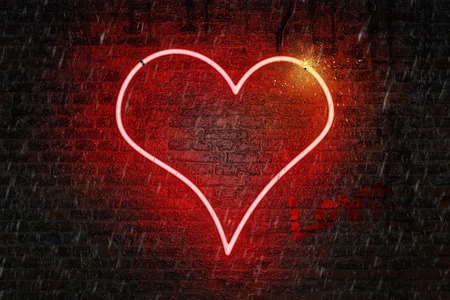 Red neon heart shaped sign on a wet brick wall, with word love written in a red paint, rain falling