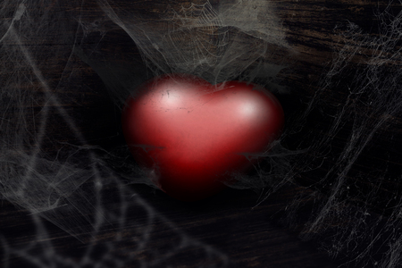 Abandoned red heart, thrown away in the corner and covered in cobwebs Stock Photo