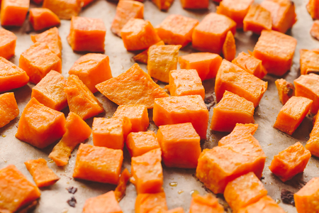 Roasted sweet potato cubes on a baking paper Stock Photo