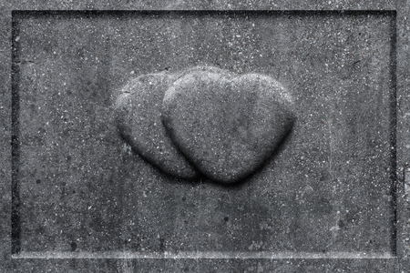 Two stone hearts carved into the tombstone