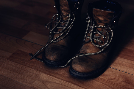Pair of warn out boots with shoelaces on a wooden floor