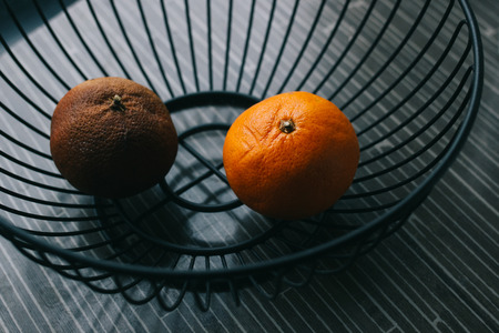 Two oranges in metal basket, one healthy and ripe, other brown and bad