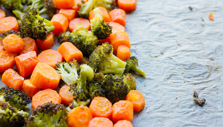 Roasted carrots and broccoli, still hot and steaming Stock Photo