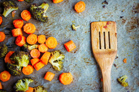 Roasted carrots and broccoli, still hot  on a baking paper with wooden spoon