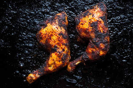 Charbroiled chicken legs and thighs, crispy and golden with charred parts on a black, charred pan