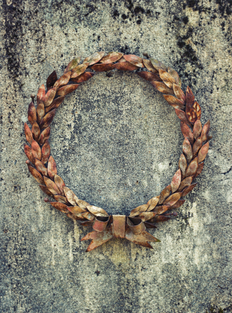 Old and weathered iron wreath on a stone tomb stone Stock Photo