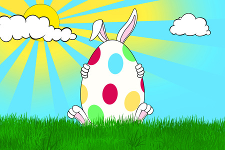 Bunny holding Easter egg decorated with colorful dots in grass field with yellow sun and white clouds on blue sky Stock Photo