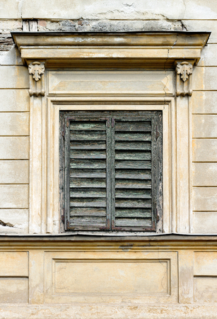 Window closed with old, wooden blinds on an old European building Stock Photo