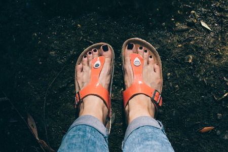 Womans feet in orange sandals and jeans standing near the lake Stock Photo